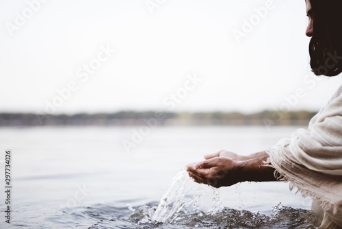 Photo Closeup shot of Jesus Christ holding water with his palms