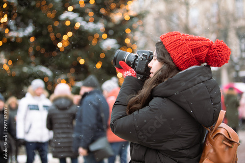 plakat woman photographer with professional camera shooting outdoors at winter time