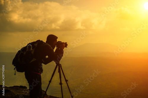 Foto auf Gartenposter Orange A male photographer travels and shoots landscapes at sunset