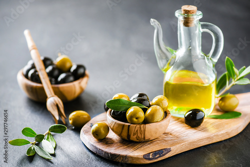 Fototapeta Ripe green and black olives on dark table with vigin oil in old glass bottle. Olive picker and leaves on wooden board. obraz