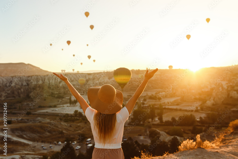 Fototapeta Beautiful young attractive girl in a hat stands on the mountain with flying air balloons on the background. Girl in the sunrise. View from the back. Famous tourist Turkish region Cappadocia.