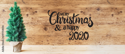 Brown Wooden Background WIth English Calligraphy Merry Christmas And A Happy 2020. Green Christmas Tree