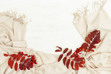 Autumn Flat Lay With Rowan Leaves Red Color And Rowanberries On Soft Autumnal Female Scarf On White Wooden Background With Copy Space. Top View.