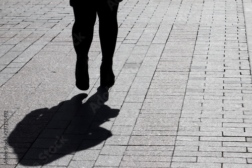 Fotografering  Silhouette of fat woman walking down the street, black shadow on pavement