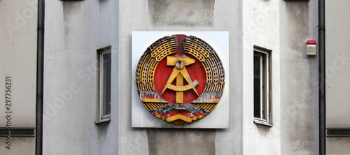 Fotomural  National emblem of East Germany (DDR) on a wall in Berlin near Checkpoint Charli