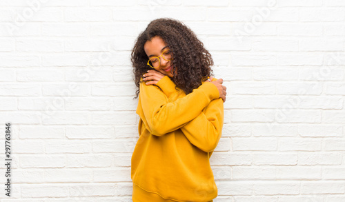 Cuadros en Lienzo young black woman feeling in love, smiling, cuddling and hugging self, staying s