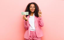 Young Black Pretty Woman With Dollar Banknotes Against Pink Wall Background