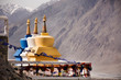 Leinwanddruck Bild - Colorful three stupa or chedi in Maitreya Buddha statue and Diskit Monastery perched against the hills at nubra valley village at Leh Ladakh in Jammu and Kashmir, India