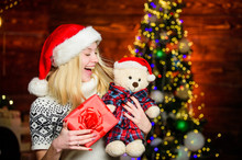 All She Wants For Christmas. Cheerful Woman. Woman Got Teddy Bear Toy Present. Santa Hat Christmas Accessory. Cute Gift. Christmas Preparation. Winter Holidays Celebration. Happy New Year. Xmas Mood