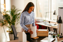 Young Businesswoman In Office Organizing Documents