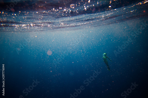 Photo girl dive underwater, blurred soft focus abstract background with plankton