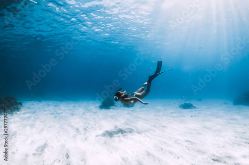 Fotomural  Attractive woman free diver glides with fins over sandy sea