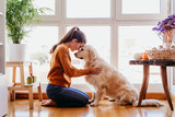 Fototapeta Dogs - beautiful woman hugging her adorable golden retriever dog at home. love for animals concept. lifestyle indoors