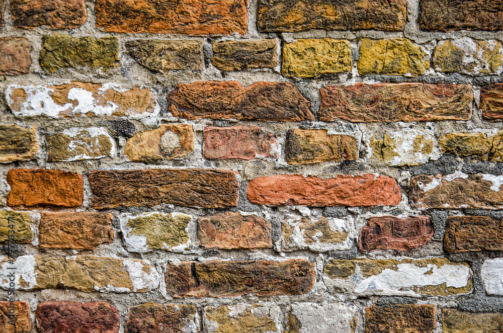 Close-up of a brick wall with colors in the range of yellow, red and brown as well as remnants of white plaster