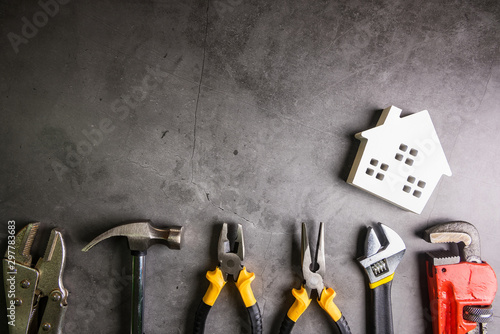 Fotografiet  Wooden house and construction tools on stone pattern background with copy space