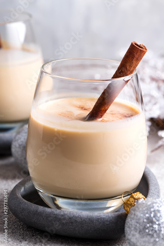 Foto auf Leinwand Alkohol Winter spicy hot drink eggnog in a glasses with cinamon in stone plate, ice frost branches on light stone table