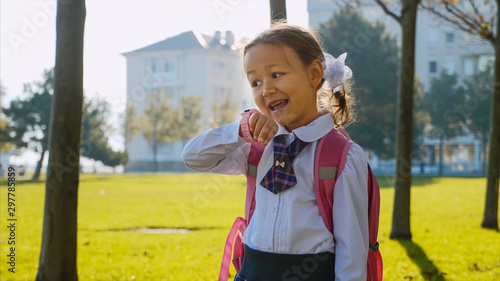 Fotografia, Obraz  Child girl in school uniform is walking quickly in the park and talking on her pink wrist smart watches and laughing at sunny autumn weather, trees along the way