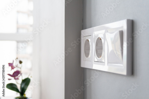 Pinturas sobre lienzo  A closeup view of a group of white european electrical outlets and a switch located on a gray wall in a light modern kitchen by the window
