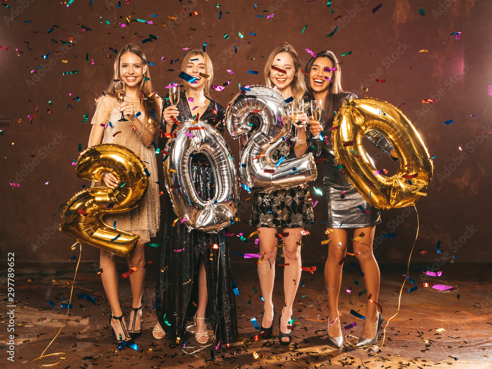 Fototapety, obrazy: Beautiful Women Celebrating New Year.Happy Gorgeous Girls In Stylish Sexy Party Dresses Holding Gold and Silver 2020 Balloons, Having Fun At New Year's Eve Party.Сarrying and drinking champagne flutes