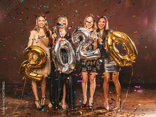 Beautiful Women Celebrating New Year.Happy Gorgeous Girls In Stylish Sexy Party Dresses Holding Gold and Silver 2020 Balloons, Having Fun At New Year's Eve Party.Сarrying and drinking champagne flutes