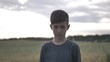 portrait of offended boy in a field looking at the camera at sunset outdoors