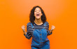 Leinwandbild Motiv young pretty black woman feeling shocked, excited and happy, laughing and celebrating success, saying wow! against orange wall
