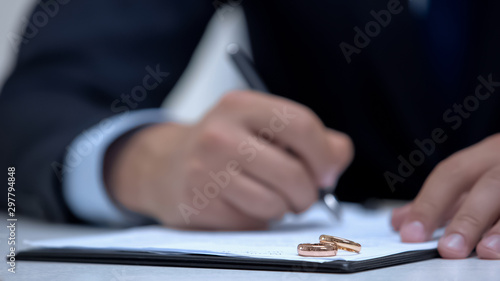Lawyer writing marriage contract, two wedding rings lying on document, divorce