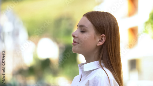 Fotografía  Inspired red-haired teenage girl inhaling pleasant aroma on city street, perfume