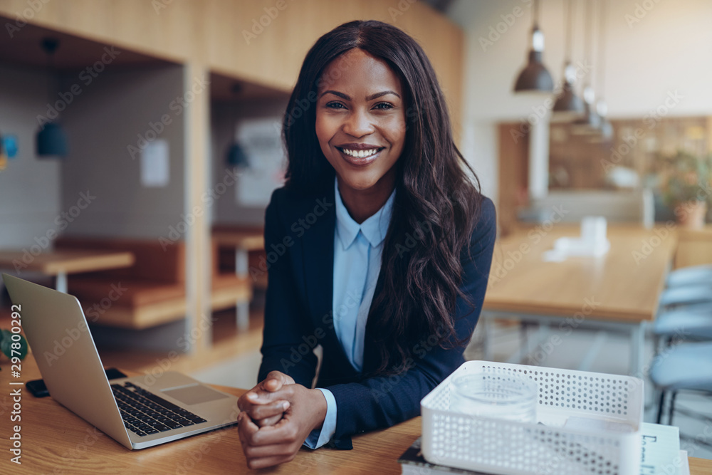 Fototapeta Smiling young African American businesswoman working in an offic