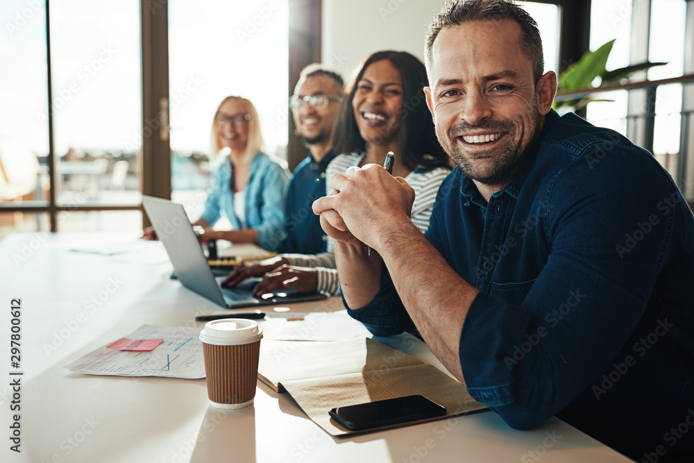 Fototapety, obrazy: Smiling mature businessman sitting with colleagues in an office