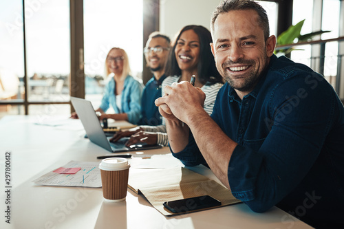 Smiling mature businessman sitting with colleagues in an office