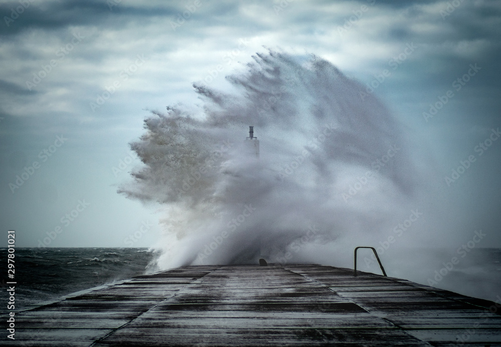 Strong winds create big waves that batter into Aberystwyth, Mid Wales sea front during the Storm season.