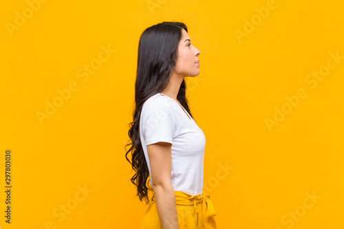 young pretty latin woman on profile view looking to copy space ahead, thinking, Canvas Print