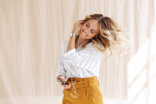 Image Of Lovely Blonde Woman In Earphones Dancing And Holding Smartphone