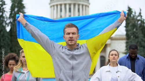 Activists raising Ukrainian flag chanting slogan, independence rally, patriotism Wallpaper Mural