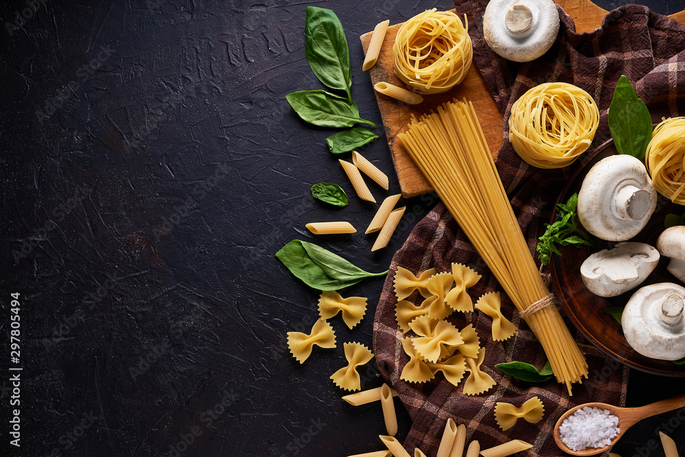 Fototapety, obrazy: ingredients for cooking traditional pasta with mushrooms on dark stone background Top view Copyspace