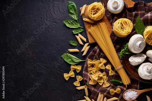 ingredients for cooking traditional pasta with mushrooms on dark stone backgroun Wallpaper Mural