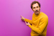 canvas print picture - young handsome man feeling shocked and surprised, pointing to copy space on the side with amazed, open-mouthed look against purple wall