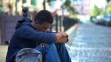Upset Multi-ethnic Boy Lonely Sitting On Sidewalk, Family Conflict, Rebellion