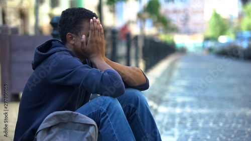 Fotografie, Obraz  Depressed Afro-American male teenager sitting on city street, escape from home