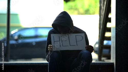 Fototapeta African-american teenager holding help cardboard sign, asking for alms in street obraz