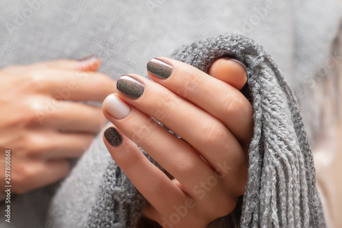 Fotografia Female hands with brown glitter nail design.