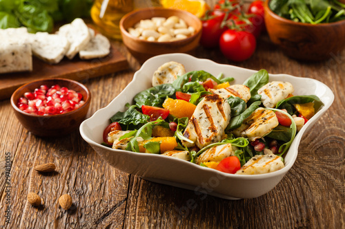 Photo Traditional Greek salad with grilled Halloumi cheese with basil