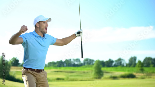 Fotografie, Obraz  Beginner golf player with club in hand rejoicing successful shot, luck and sport