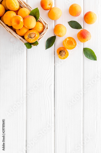 Fresh raw apricots in basket on white wooden background top view copy space, pat Canvas Print