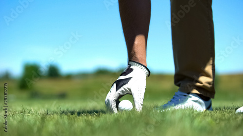 Male golfer teeing off golf ball before swing, professional and luxury sport Slika na platnu
