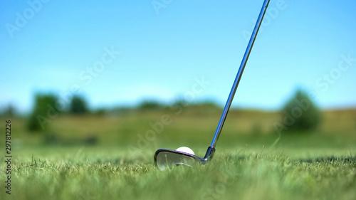 Valokuva  Iron golf club hitting white ball on course, professional sport, elite hobby