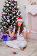 A young, beautiful girl in white clothes and a red cap sits in a lotus position on the fur with a toy trolley and Christmas balls in her hands against the background of a Christmas tree and fireplace.