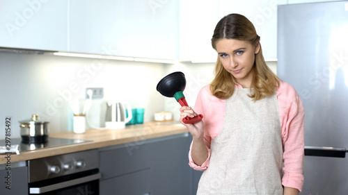 Valokuva  Dissatisfied housekeeper showing plunger, tool to unclog drain, plumber service