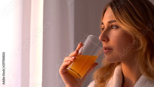 Girl in robe drinks orange juice looking in window, vitamins for skin, face care Fototapeta